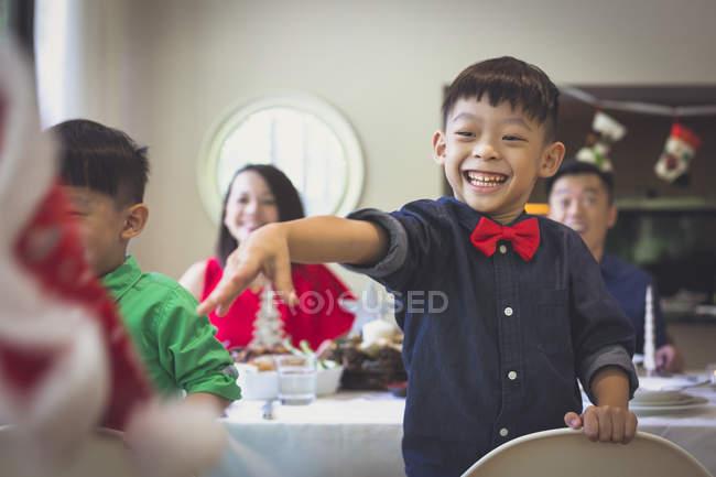 Ragazzino si sta divertendo durante la cena e getta via il suo cappello di Natale in un umore gioioso . — Foto stock