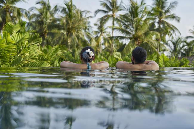 Giovane coppia asiatica di turisti rilassante in piscina — Foto stock