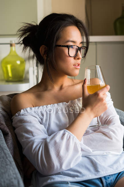 Young chinese woman drinking wine and wearing glasses — Stock Photo