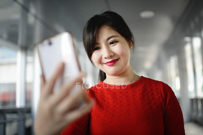 Joven hermosa asiático mujer usando smartphone - foto de stock