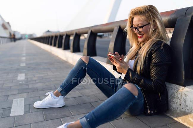 Retrato de una hermosa joven usando su teléfono móvil en la calle. - foto de stock