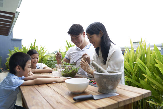 Happy asian family preparing food together at home — Stock Photo