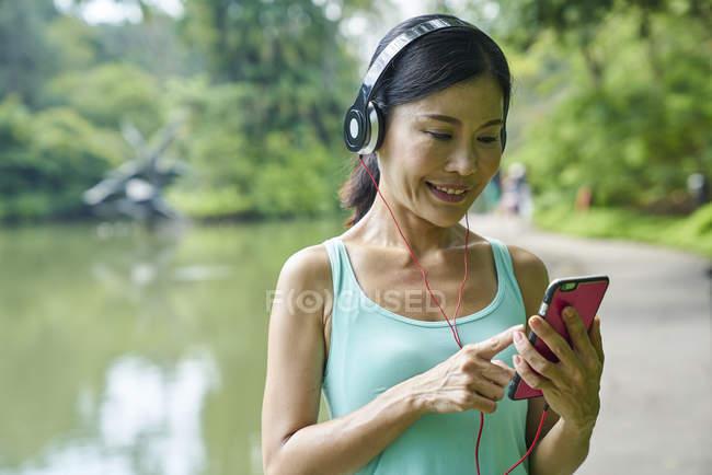 Retrato de mulher de meia-idade ouvindo música enquanto caminha em Jardins Botânicos — Fotografia de Stock