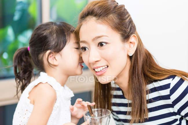Маленька дівчинка, Шепіт у вухо матері. — стокове фото