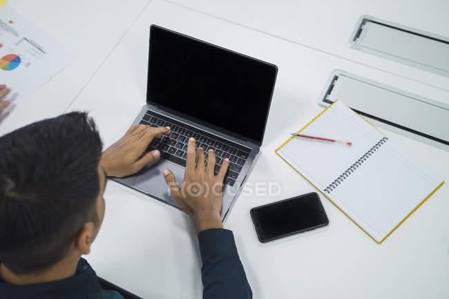 Uomo di affari asiatica giovane lavora con il computer portatile in ufficio moderno — Foto stock