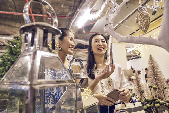 Two young asian woman shopping together in mall at christmas — Stock Photo