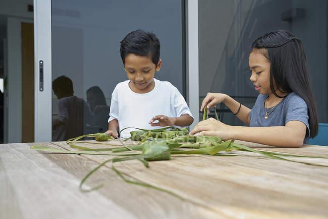 Jeunes frères et sœurs asiatiques célèbrent Hari Raya ensemble à la maison et faire des décorations — Photo de stock