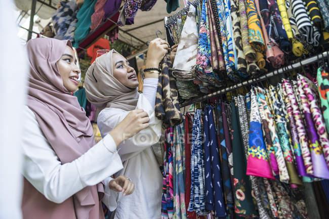 Due signore musulmane che fanno shopping per hijab . — Foto stock