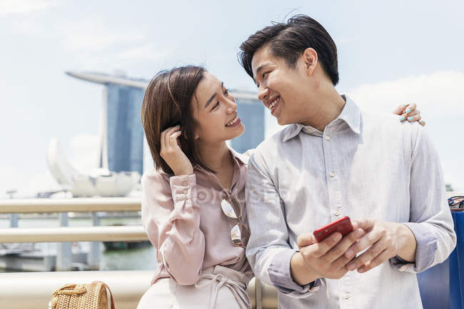 Young asian couple sharing smartphone together in Singapore — Stock Photo