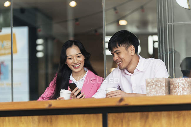 Attractive young asian couple drinking coffee and using smartphone — Stock Photo