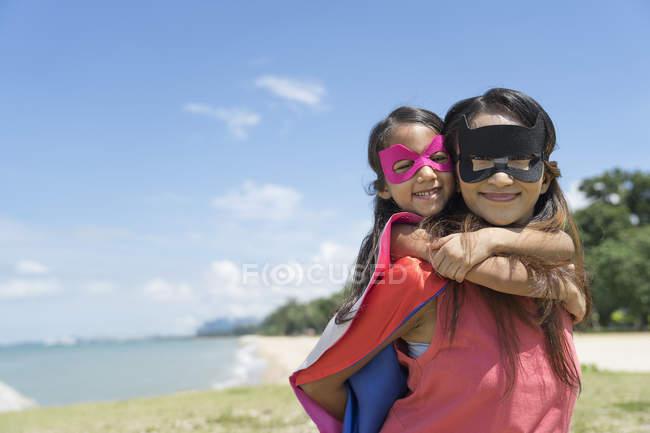 Mãe carregando criança super-herói na praia — Fotografia de Stock