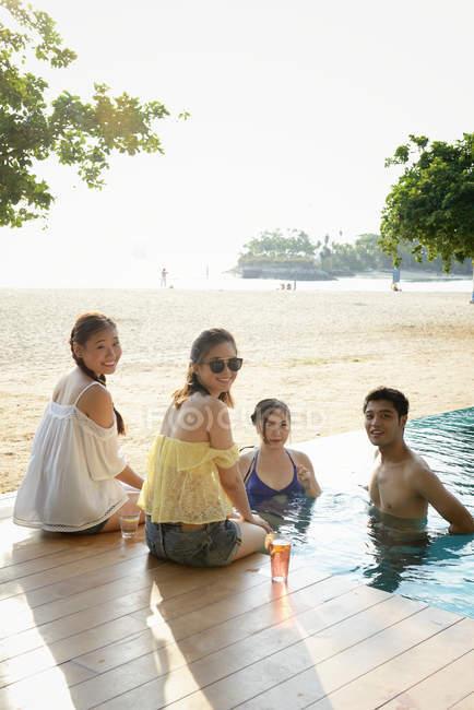 Beautiful young asian friends relaxing near pool — Stock Photo