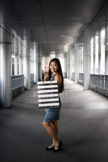 Joven asiático mujer en comercial mall smilng a cámara - foto de stock