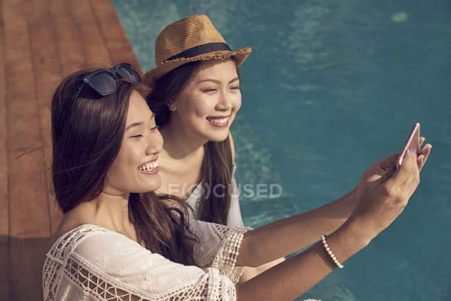 Attraktive junge asiatische Frauen, die die Selfie Pool — Stockfoto