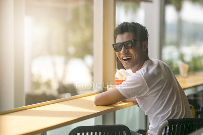 Un hombre singapurense de pelo negro está tomando una copa por la tarde solo en un resort de playa Sentosa . - foto de stock
