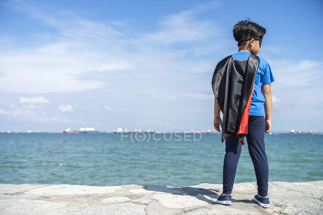 Rear view of superhero kid standing against sea — Stock Photo