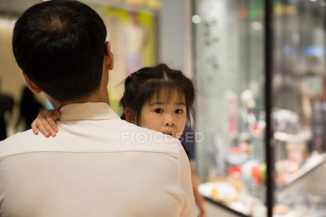El padre lleva a su hija en un centro comercial. - foto de stock