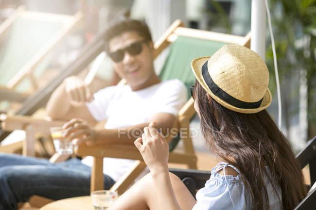 Freunde, die einen Spaß Unterhaltung auf der Terrasse von einem Beach-Club in Singapur — Stockfoto