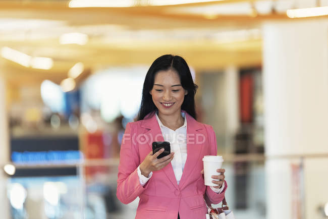 Young attractive asian woman using smartphone in shopping mall — Stock Photo