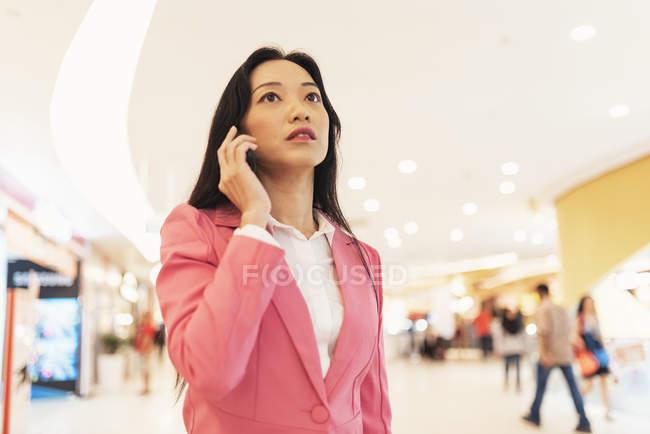 Joven atractivo asiático mujer usando smartphone en centro comercial - foto de stock
