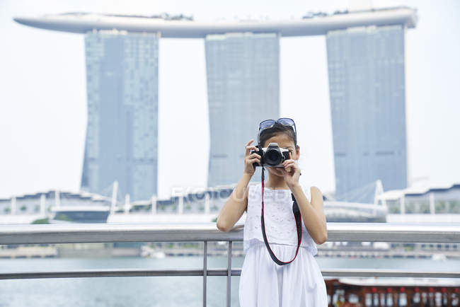 Young girl shooting on her camera at Raffles Place, Singapore — Stock Photo