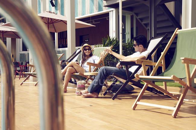 Atraente jovem casal asiático relaxante perto da piscina — Fotografia de Stock