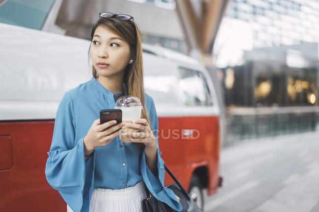 Attraktive junge asiatische Mädchen mit Smartphone und Kaffeetasse — Stockfoto