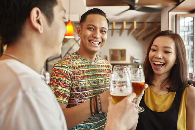 Jovens amigos asiáticos com cerveja junto no bar — Fotografia de Stock