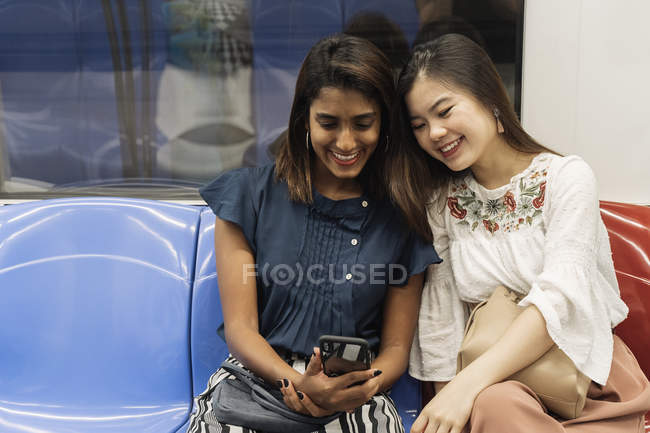 Young casual asian girls sharing smartphone in train — Stock Photo