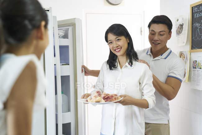 Feliz asiático familia, madre mostrando comida hija - foto de stock