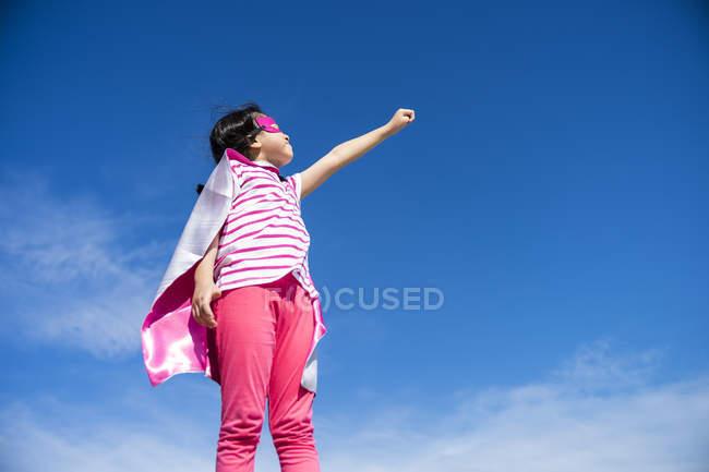 Bonito pouco super-herói menina em máscara e casaco posando contra o céu — Fotografia de Stock
