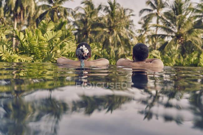 Rear view of young couple relaxing in a pool — Stock Photo