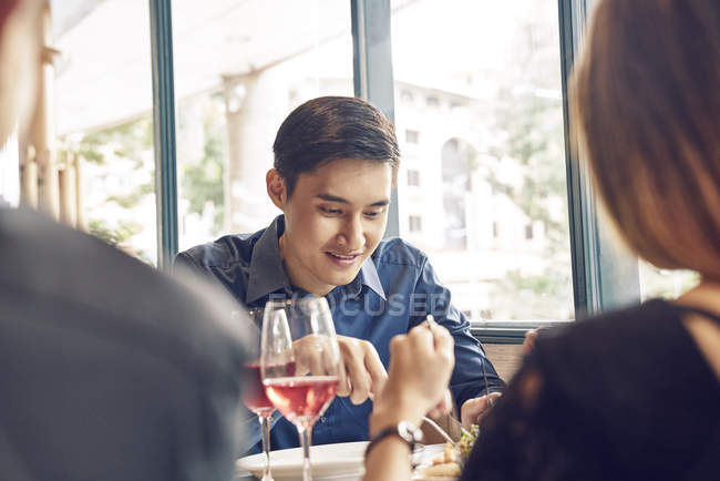 Company of young asian friends eating in cafe — Stock Photo