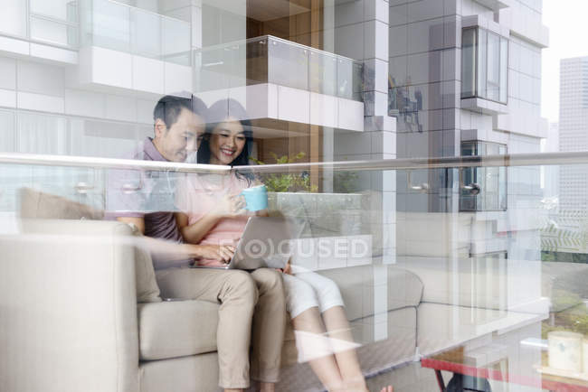 Mature asian casual couple using laptop together — Stock Photo