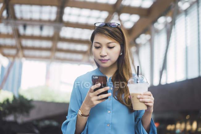 Attrayant jeune fille asiatique en utilisant smartphone et tasse de café — Photo de stock