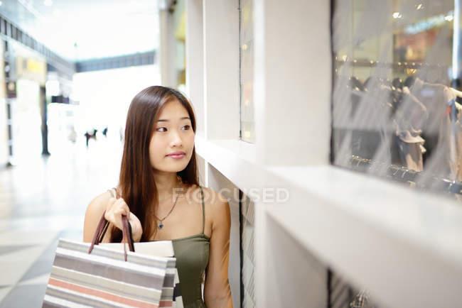 Joven asiático mujer en comercial centro comercial de pie cerca de tienda frente - foto de stock