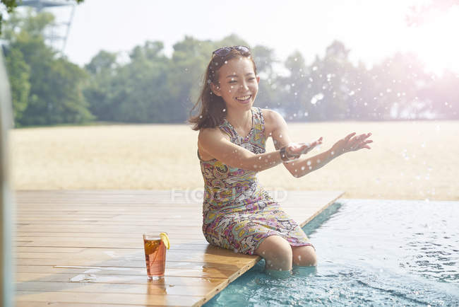 Young beautiful asian woman splashing water near swimming pool — Stock Photo