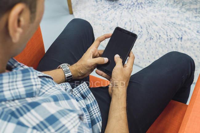Homem de negócios asiáticos jovens usando smartphone no escritório moderno — Fotografia de Stock