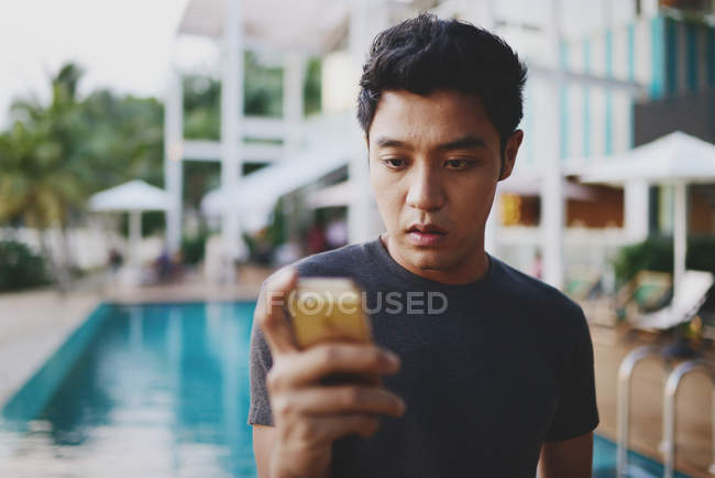 Young attractive asian using smartphone against pool — Stock Photo