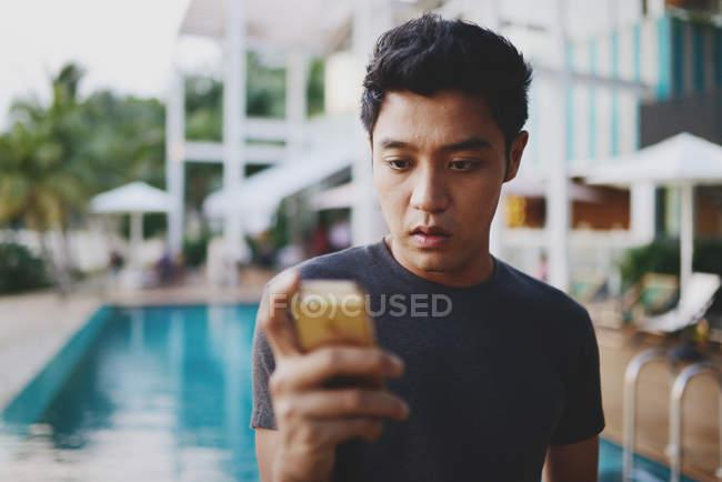 Jovem asiática atraente usando smartphone contra piscina — Fotografia de Stock