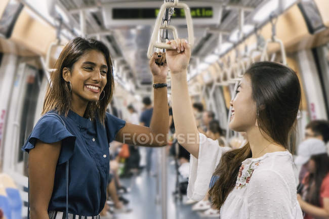 Young casual asian girls smiling in train — Stock Photo