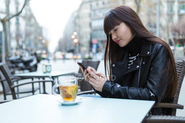 Femme dans un café avec son smartphone — Photo de stock