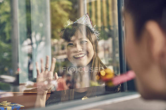 Young asian woman looking through window at friend — Stock Photo