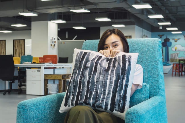 Young asian business woman holding pillow in modern office — Stock Photo