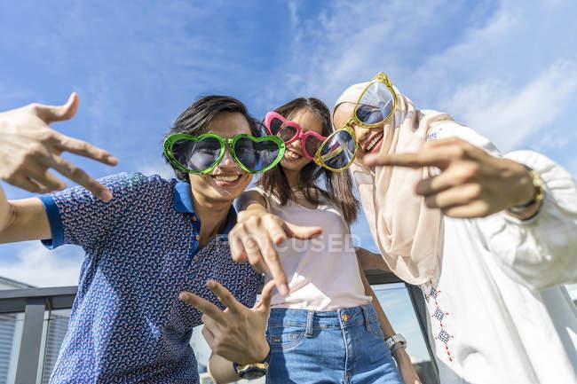 Gruppe von Freunden mit lustigen Brillen amüsiert sich vor blauem Himmel — Stockfoto