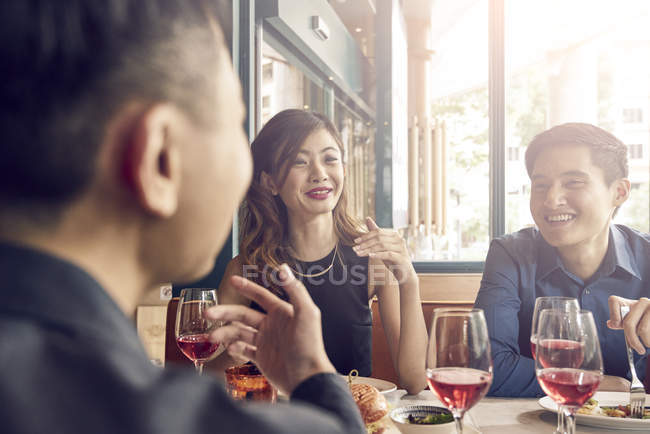 Company of young asian friends together in restaurant — Stock Photo
