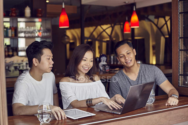 Young asian friends using laptop together in bar — Stock Photo