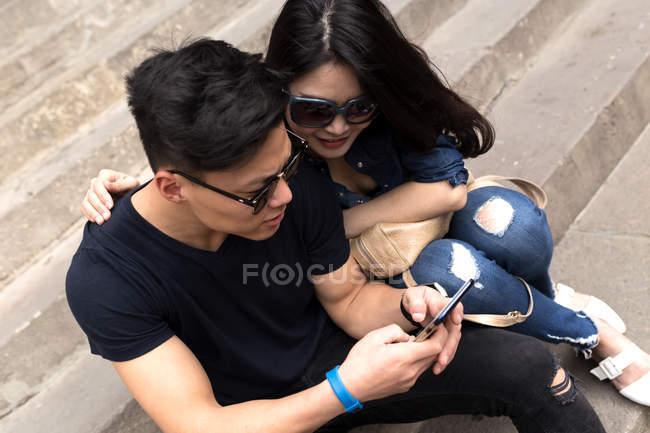 Schöne junge asiatische Paar sitzt auf Stufen mit Smartphone — Stockfoto