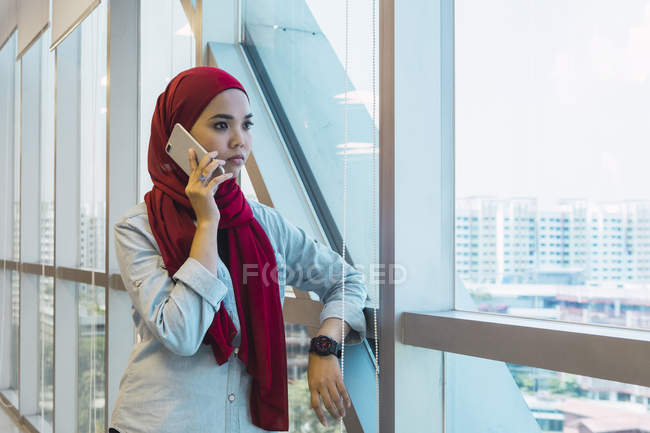 Young asian business woman talking on smartphone in modern office — Stock Photo