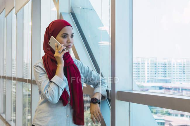 Молодых азиатских бизнес женщина говорить на смартфон в современном офисе — стоковое фото
